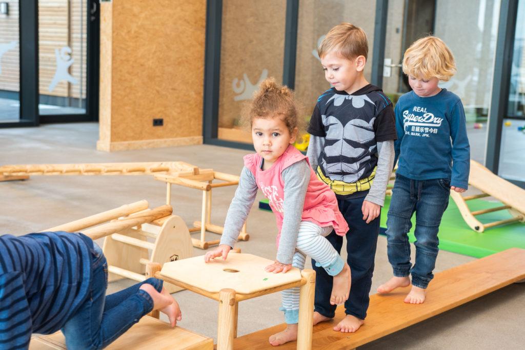 Kletternde Kinder im Innenhof des campus kinderhaus